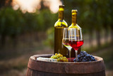 Pair of wine glasses and bottles on old barrel with bunch of grapes - 199175849