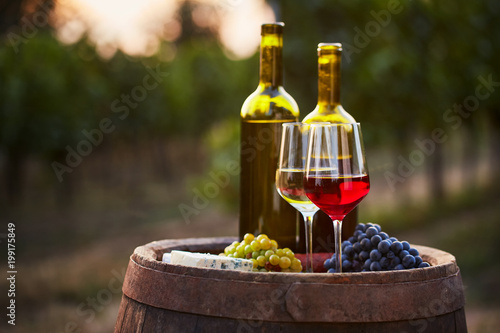 Deurstickers Wijngaard Pair of wine glasses and bottles on old barrel with bunch of grapes