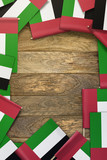United Arab Emirates small flags framing a wood texture background with copy space