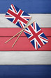 Two United Kingdom flags on a red white and blue painted wood background