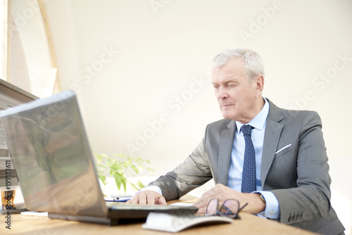 Portrait of an elderly businessman wearing suit while sitting at office desk in front of laptop.