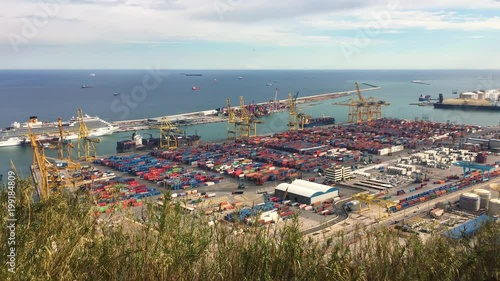 Time lapse of the port of Barcelona. There is a lot of activity of trucks and cargo boats.