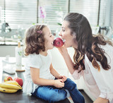 Mother and daughter biting an apple - 199186831