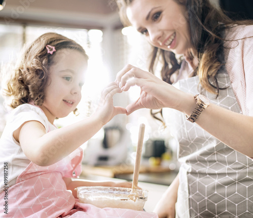 Fotobehang Artist KB Cheerful mother and daughter having fun in the kitchen