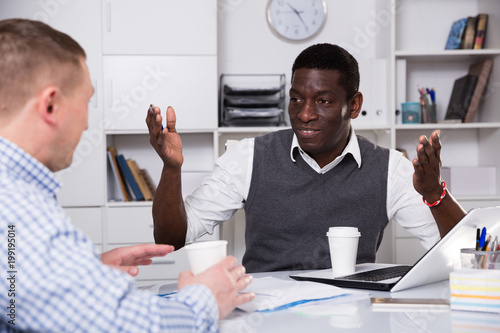 Happy man with coworker drinking coffee in office