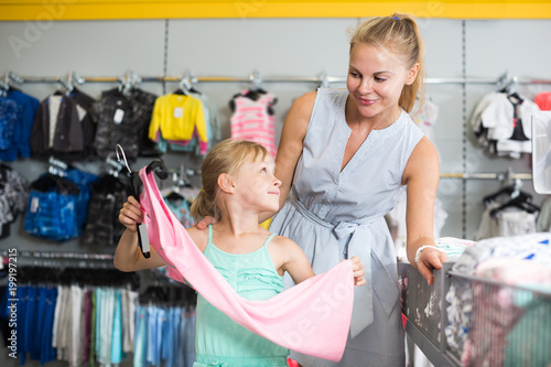 Portrait of glad mom with child choosing dress