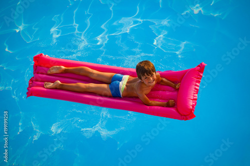 Smiling boy swimming on pink inflatable mattress