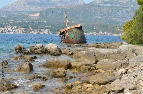 Fotobehang Schipbreuk Ship wreck stranded on sea rocks and a seascape