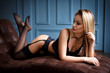 Beautiful girl in a sexy black lingerie on sofa