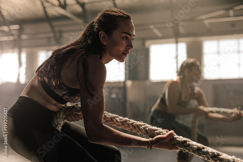 Poster Women exercising with rope at a gym