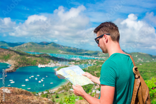 Aluminium Young tourist man with map background of English Harbor from Shirley Heights, Antigua, paradise bay at tropical island in the Caribbean Sea