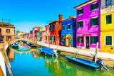 Venice landmark, Burano island canal, bridge, colorful houses and boats, Italy.