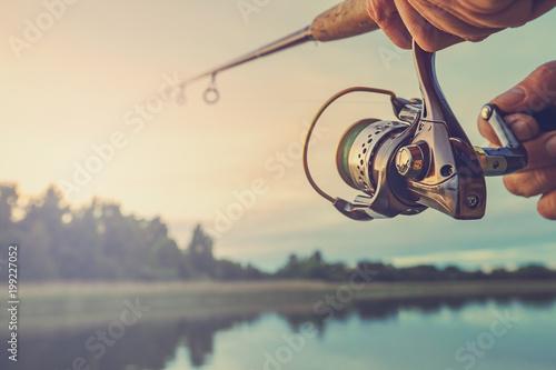 Leinwandbild Motiv Fishing on the lake at sunset. Fishing background.