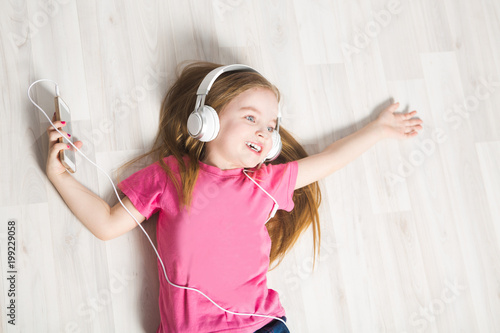 Child girl with headphones and smartphone listening to music lying on floor.