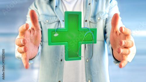 Foto Murales Businessman holding a Lighting pharmacy cross and a stethoscope - 3d render