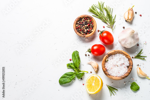 Spices and herbs over white stone table top view.