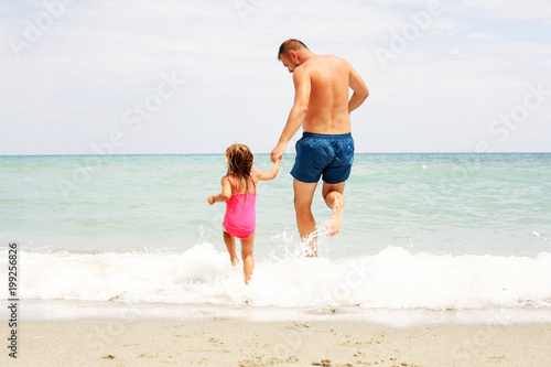 Foto op Plexiglas Amusementspark Father and daughter running in the sea.