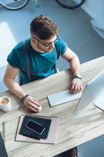 Fridge magnet overhead view of young freelancer in eyeglasses working with desktop computer