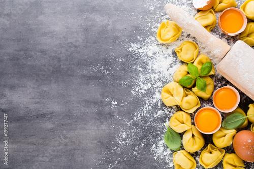Homemade raw Italian tortellini and basil leaves. - 199277417