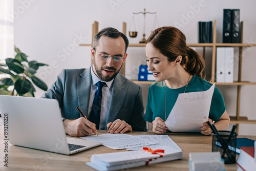 portrait of lawyer in eyeglasses and client discussing contract at workplace with laptop in office