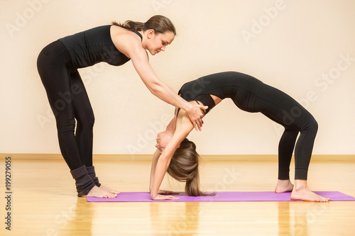 Foto op Aluminium School de yoga Instructor is helping young woman make yoga asana at gym.