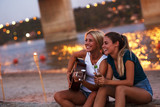 Two young female friends sitting by the river,singing and playing guitar.Joying in summer evening .
