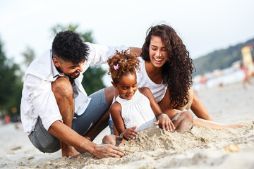 Young mixed race family sitting and relaxing at the beach on beautiful summer day.Playing in the sand.