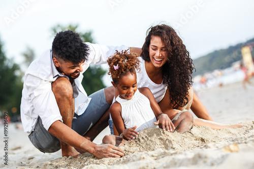 Młoda rodzina mieszanej rasy siedzi i relaks na plaży w piękny letni dzień. Gry w piasku.