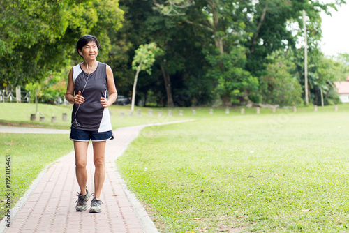Poster Jogging Front view of senior Asian woman jogging through park