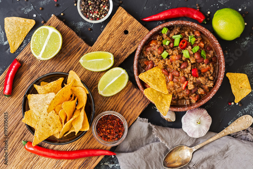 Chili con carne.Mexican chili food with meat and corn chips nachos on a rustic background. View from above. - 199305635
