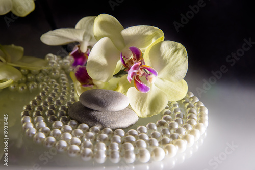 Foto op Plexiglas Spa flat stones on a white glass on the background of yellow orchids