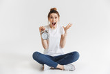 Portrait of a shocked young girl holding alarm clock - 199313856