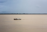 Typical boat sails on the river before a storm in the Amazon.
