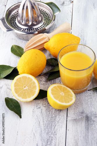 Plexiglas Sap Glass of lime juice and slices of orange fruit on wooden background.