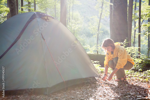Foto Murales Tourism concept. Camping and hiking.  Woman setting tent in the forest summer day in the sunlight