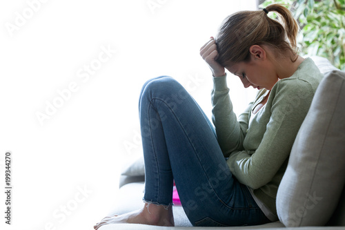 Unhappy lonely depressed young woman sitting on sofa at home. Depression concept.