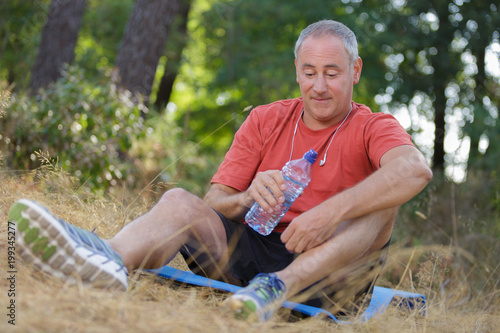 senior male jogger relaxing after exhausting training in the woods
