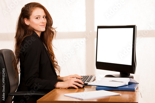 beautiful young business woman work at her desk in the office with window in the background