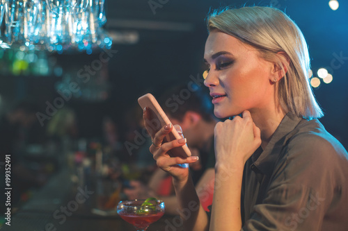 Side view pensive female typing in mobile while tasting alcohol liquid. Technology and rest in club concept