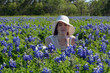 Bluebonnet Bonnet/Young woman in white dress and sun hat, laying in a field of Texas Bluebonnet Wildflowers.