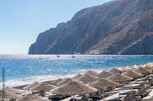 Keuken foto achterwand Santorini beach with umbrellas and deck chairs by the sea in Santorini