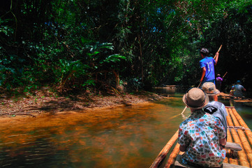 Boys (8 years old) floating along tropical river on bamboo raft in jungle. Concept traveling with children back view. Copy space.