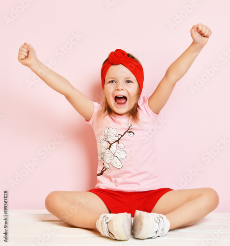 Cute baby girl kid in light pink pajamas and red headband with raised hands