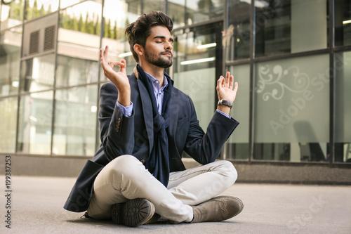 Arabian businessman practicing yoga in the city.