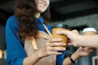 Young asian woman barista serving a disposable coffee cup to customer at cafe counter background, small business owner, food and drink industry concept