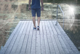 Man walks on wooden pier at lake with futuristic cyberspace network background.