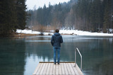 Back view of a man stands on wooden pier at cold winter seasonal lake. - 199398606