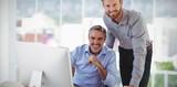 Composite image of portrait of smiling businessmen at desk