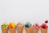 Various of ice cream flavor in cones blueberry ,strawberry ,pistachio ,almond ,orange and cherry setup on white wooden background . Summer and Sweet menu concept. - 199405433