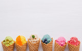 Various of ice cream flavor in cones blueberry ,strawberry ,pistachio ,almond ,orange and cherry setup on white wooden background . Summer and Sweet menu concept. - 199405452